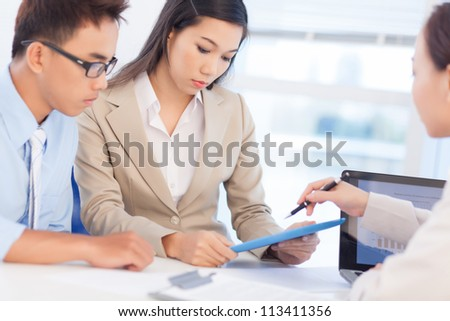 Group of young professionals holding a meeting to draw up the results of the financial period - stock photo