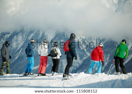 Group of young skiers stands on edge of snowy hillslope - stock photo
