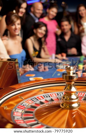 group of young smiling people looking excited at spinning roulette - stock photo