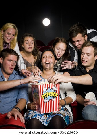 Group of young spectators eating popcorn at the movie theater - stock photo