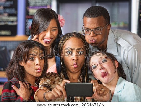 Group of young students making faces on phone - stock photo