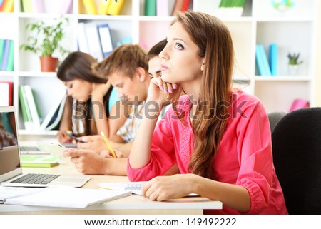 Group of young students sitting at the library - stock photo