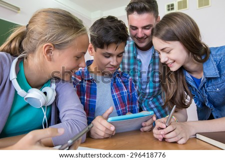 group of young students studying in the classroom with tablet