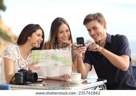 Group of young tourist friends consulting gps map in a smart phone in a restaurant with the beach in the background - stock photo