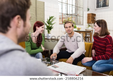 Group of Young White Friends Relaxing at the Living Room Area While Sharing Happy Moments. - stock photo