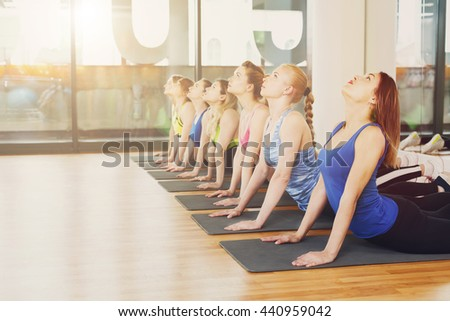 Group of young women in yoga class making exercises. Girls do back stretching. Healthy lifestyle in fitness club - stock photo