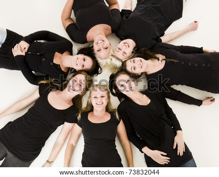 Group of Young Women lieing in a circle on white background