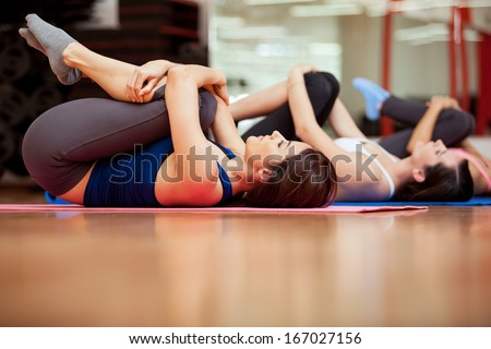 Group of young women stretching and warming up for a gym class - stock photo