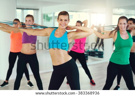 Group of young women stretching arms in studio