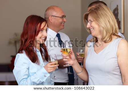 Group of 4 younger and older businesspeople celebrate with wine glasses in their hands - stock photo