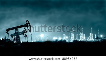 Group oil rigs and brightly lit industrial site at night. Toned. - stock photo