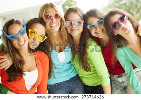 Group on young female friends having fun, wearing funny glasses - stock photo