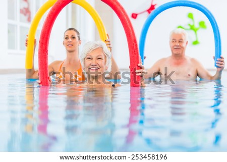 Group  or young and senior people in aquarobic fitness swimming pool exercising with  pool noodle - stock photo