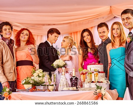 Group people at wedding table with cake. In the center of bride and groom - stock photo
