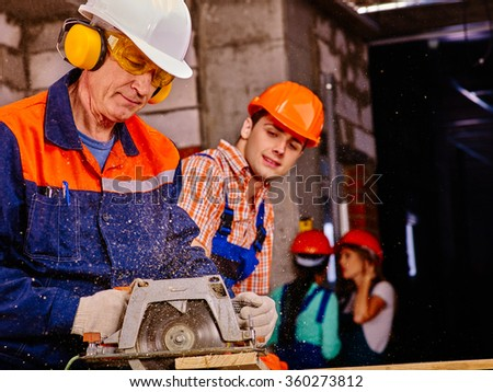 Group people  builder with circular saw . - stock photo