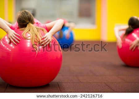 Group people in a pilates class at the gym - young woman with gymball at fitness training (shallow DOF, color toned image) - stock photo