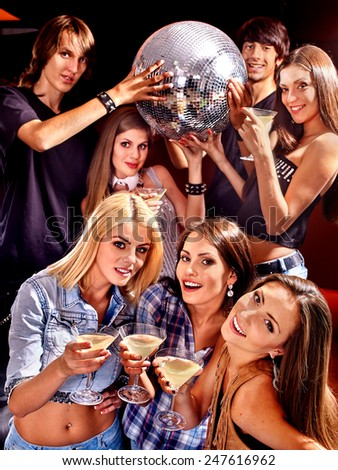 Group people  on disco in night club. Girls holding disco ball