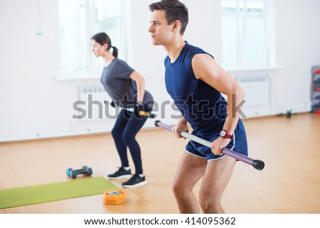 Group people warming up, doing power exercise workout in fitness club. - stock photo