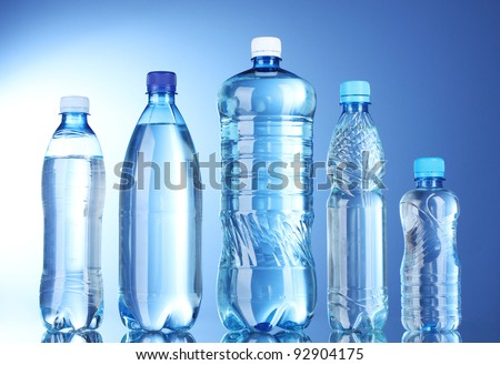 Group plastic bottles of water on blue background - stock photo