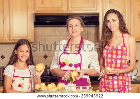 Group portrait happy, smiling mother and her daughters cooking dinner, preparing food at home in a kitchen. Positive family emotions, face expression, life perception. Healthy eating concept - stock photo