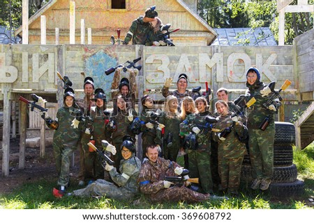 Group portrait of big happy company playing paintball and sign White Castle on background - stock photo
