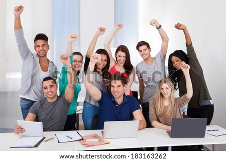 Group portrait of happy multiethnic college students celebrating success in classroom - stock photo