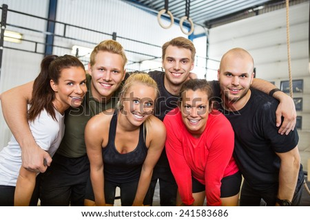 Group portrait of happy people standing together at cross training box - stock photo