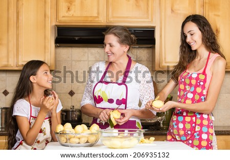 Group portrait of happy, smiling mother and daughter cooking dinner, preparing food isolated background home kitchen. Positive family emotions, face expression, life perception. Healthy eating concept