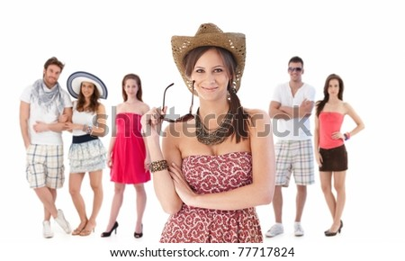 Group portrait of happy young people dressed for summer. Young women at front holding sunglasses.? - stock photo