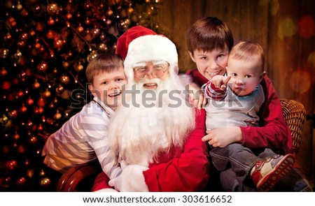 Group portrait of Kind Santa Claus sitting with Happy Children.