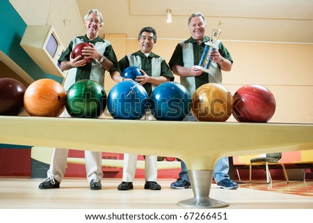 Group portrait of men with bowling balls - stock photo