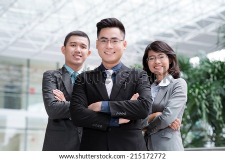 Group portrait of smiling professional business team looking at the camera - stock photo