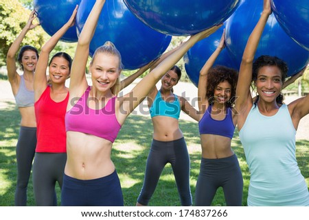 Group portrait of sporty women exercising with fitness balls at park
