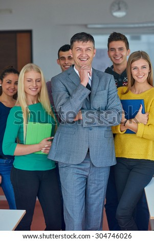 group portrait of teacher with students in shcool classrom - stock photo