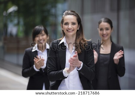 Group portrait of three female executives clapping hands during a business meeting - stock photo