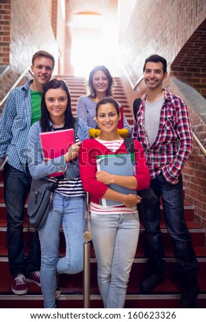 Group portrait of young college students standing on stairs in the college - stock photo