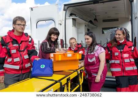 Group positive paramedics with medicine chest on ambulance emergency background - stock photo