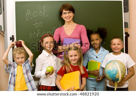 Group schoolchildren looking at camera with their teacher near by - stock photo
