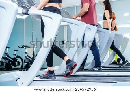 Group sessions on the treadmill. Sports people running on the treadmill at the gym. Athletes wearing sportswear and running in the gym a rear view athletes. - stock photo