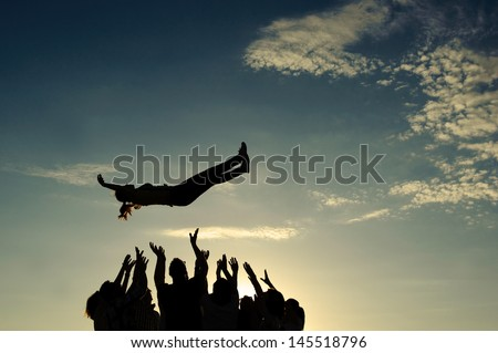 Group throwing girl in the air - stock photo