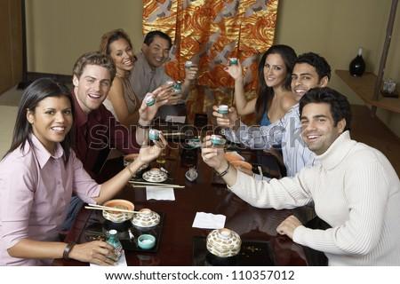 Group toasting Japanese saki cups in restaurant - stock photo