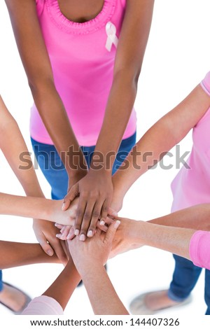 Group wearing pink and ribbons for breast cancer putting hands together on white background - stock photo