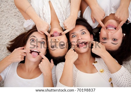 Group women lying on the floor making funny faces - stock photo