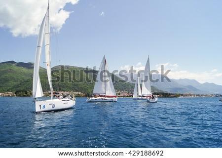 "Group yachts off the coast. Tivat, Montenegro - 26 April, 2016. Regatta ""Russian stream"" in God-Katorskaya bay of the Adriatic Sea off the coast of Montenegro. - stock photo"