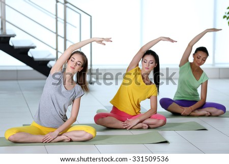 Group yoga exercise for young women - stock photo
