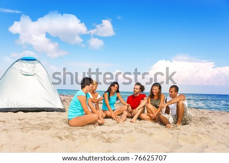 group young people camping together on beach