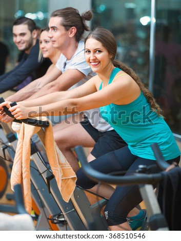 Group young working out of cycling in modern fitness club