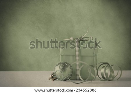 Grouping of Christmas bauble and swirly ribbon with a  gift box tied to a bow with gingham.  Faded green with parchment background and vignette for vintage effect. - stock photo