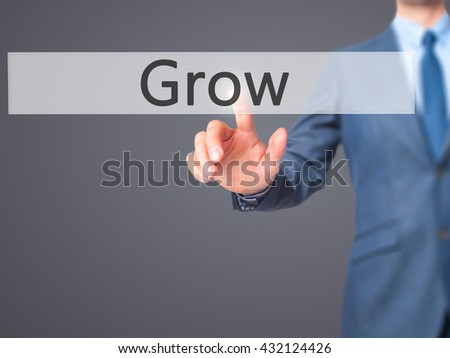 Grow - Businessman hand pressing button on touch screen interface. Business, technology, internet concept. Stock Photo - stock photo