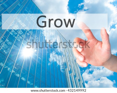 Grow - Hand pressing a button on blurred background concept . Business, technology, internet concept. Stock Photo